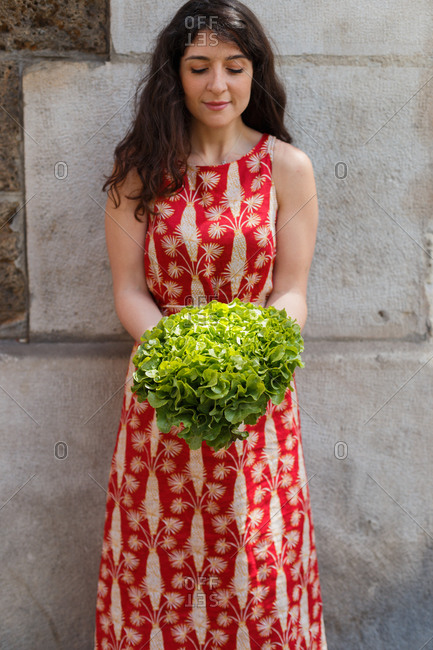 Tranquil female in summer dress standing near stone building with bunch of ripe green lettuce and looking down
