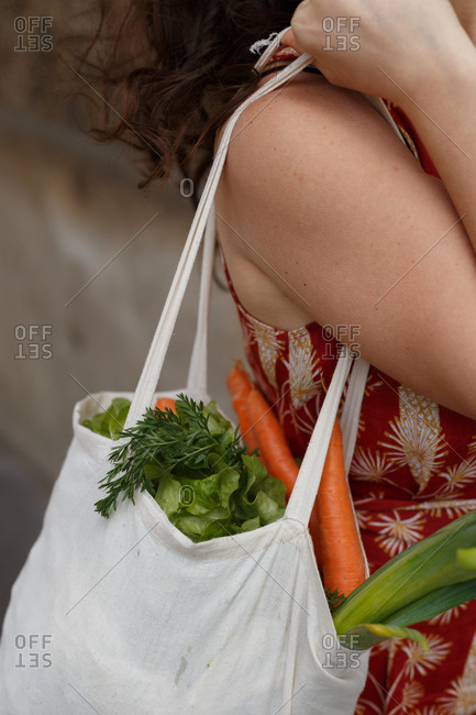 Side view cropped unrecognizable female standing with reusable shopping bag full of groceries during coronavirus epidemic