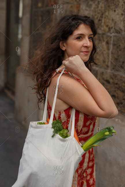 Side view of female standing with reusable shopping bag full of groceries during coronavirus epidemic