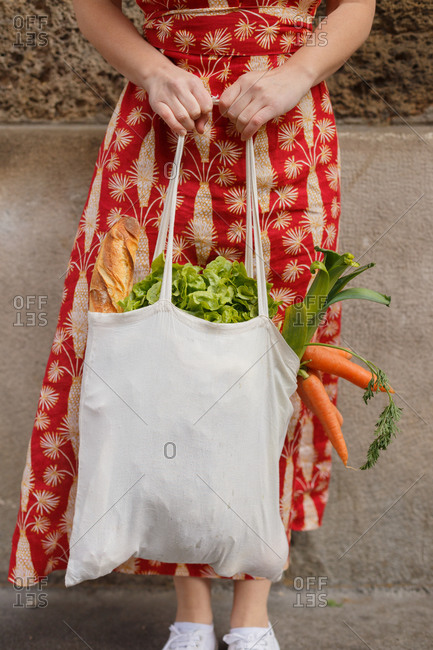 Cropped unrecognizable female standing with reusable shopping bag full of groceries during coronavirus epidemic