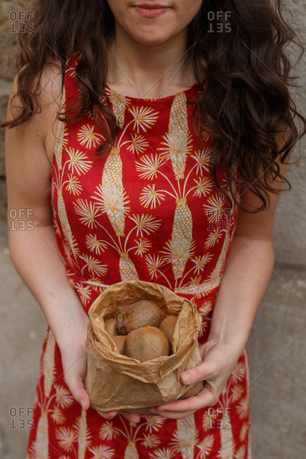High angle of unrecognizable female standing with paper bag full of ripe kiwi on background of stone wall in city