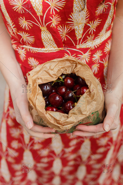 High angle of unrecognizable female in dress with ripe cherry in paper bag