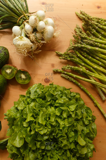 From above of various tasty vegetables and greenery placed on wooden table in kitchen