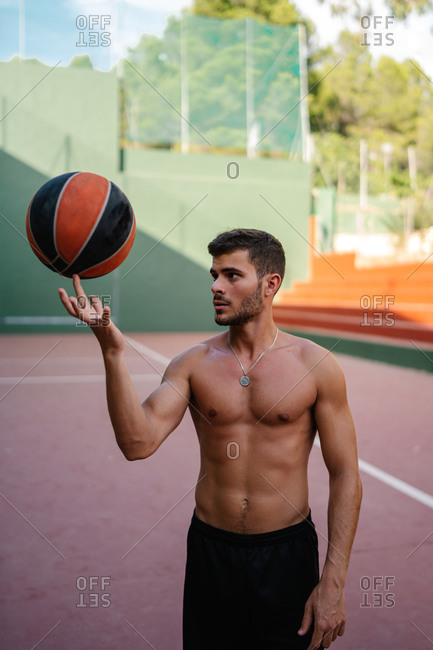 Determined sportsman with naked torso standing on playground in summer and spinning ball on finger