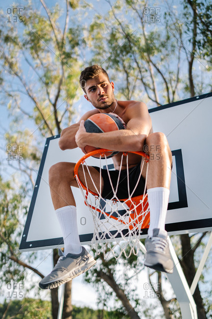 From below of male athlete in sportswear sitting on basketball hoop with ball and looking away