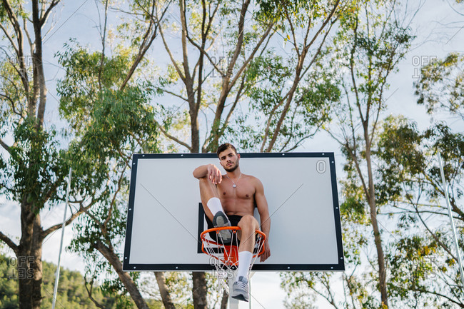From below of male athlete in sportswear sitting on basketball hoop looking at camera