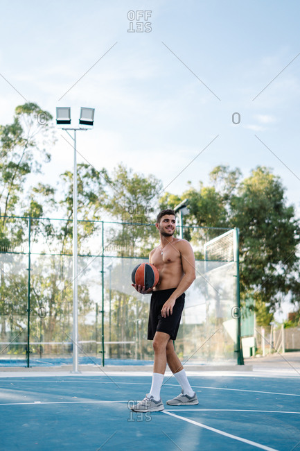 Concentrated male athlete with naked torso playing basketball alone on sports ground in summer
