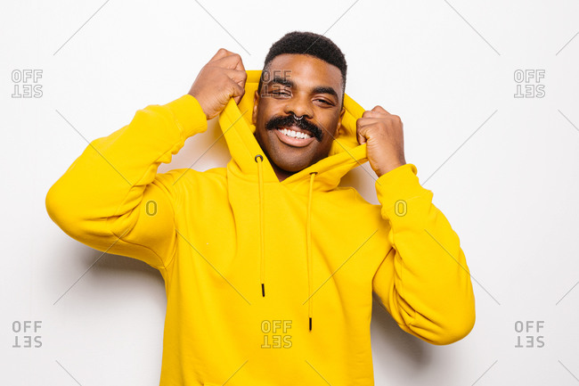 Cheerful black man over white plain background. He is looking at camera and smiling wearing a yellow hoodie