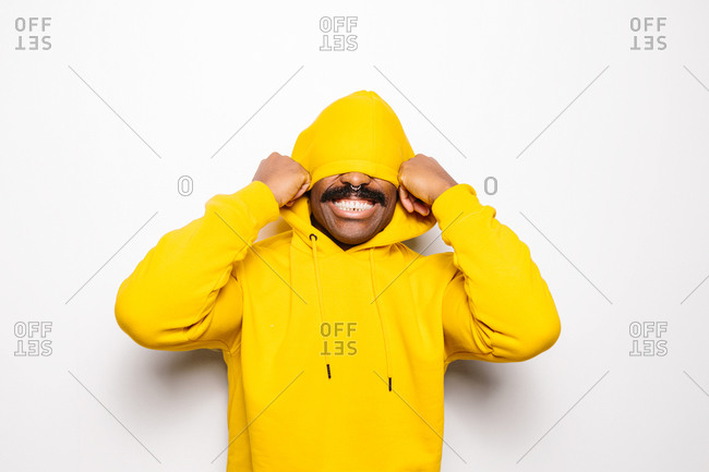 Cheerful black man over white plain background. He is looking at camera and smiling wearing a yellow hoodie. He is covering his face with the hood.