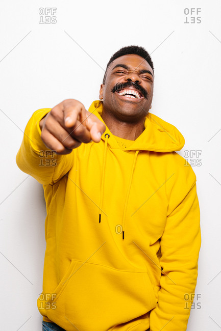 Cheerful black man over white plain background. He is pointing to camera and laughing wearing a yellow hoodie