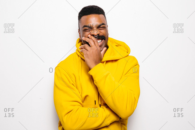 Cheerful black man over white plain background. He is looking at camera and laughing wearing a yellow hoodie
