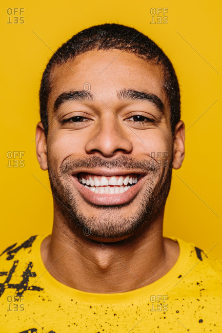 Portrait of cheerful man smiling and looking at camera over plain yellow background