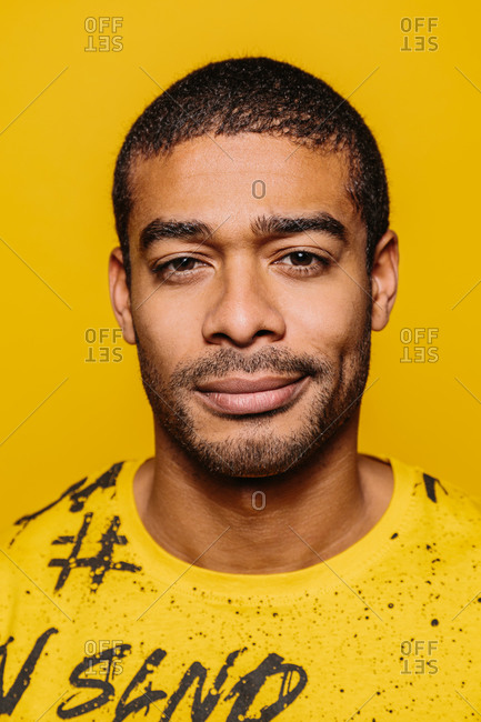 Mixed race young man looking at camera with serious expression over yellow background