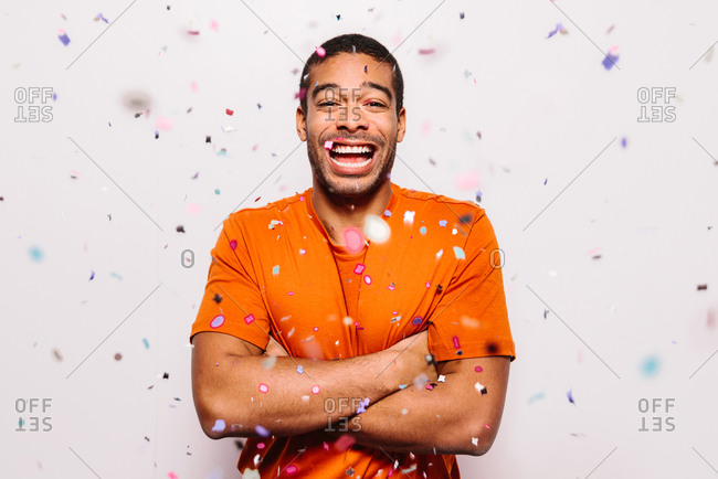 Cheerful man isolated on white background. He is wearing an orange t-shirt with arms crossed and looking at camera while falling confetti on him