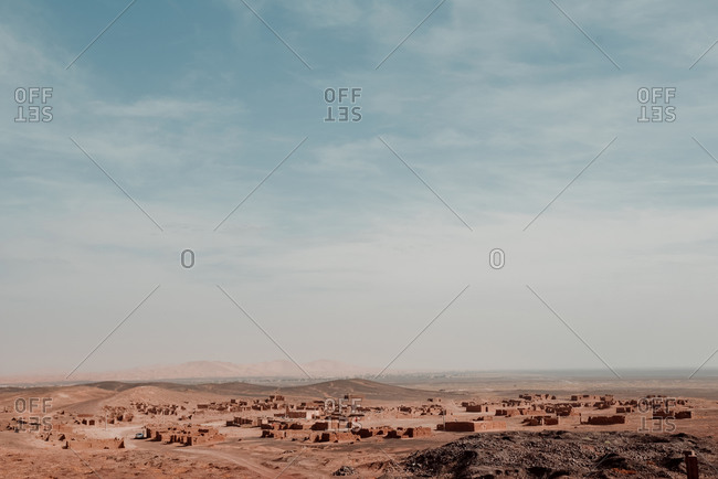 Distant small village located in dry desert terrain under cloudy blue sky in Morocco
