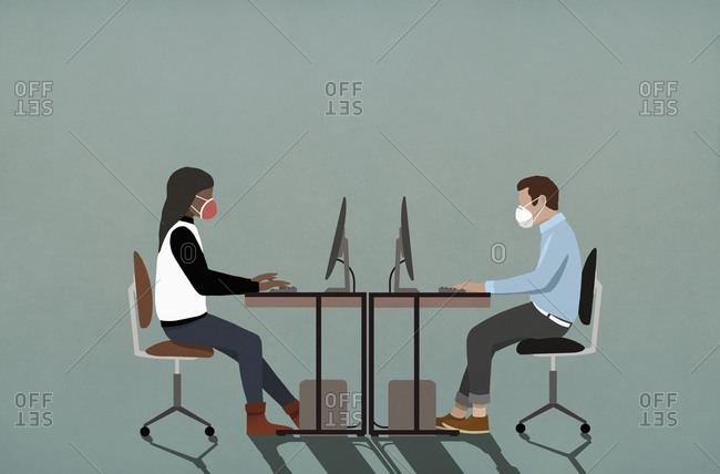 Business people in face masks working at computers