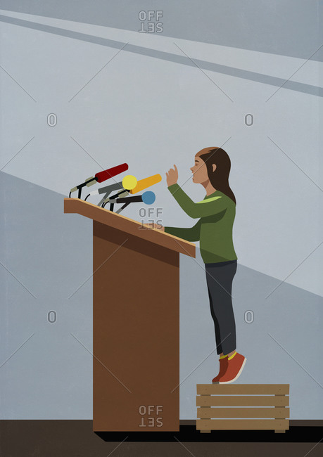 Girl standing on crate at podium with microphones