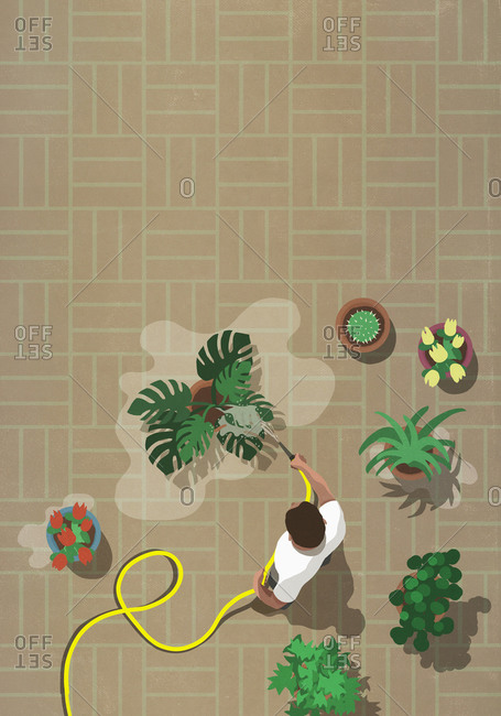 Man watering patio plants with hose
