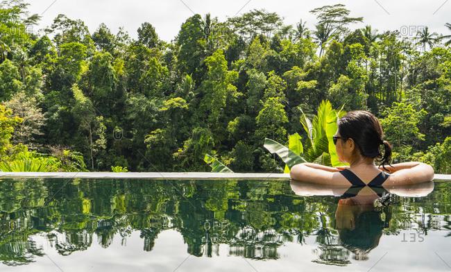 Woman enjoying view in infinity pool, Ubud, Bali, Indonesia