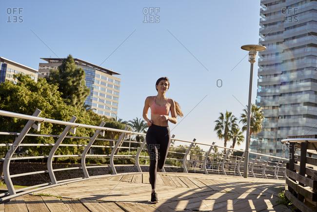 Woman jogging in city park, Barcelona, Catalonia, Spain