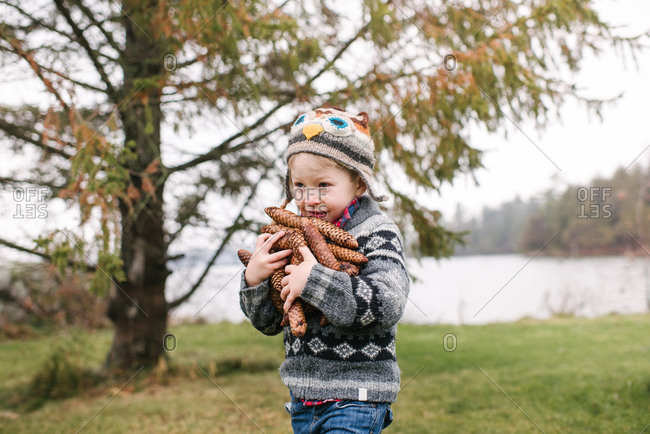 Boy with armful of brown pine cones, Kingston, Ontario, Canada