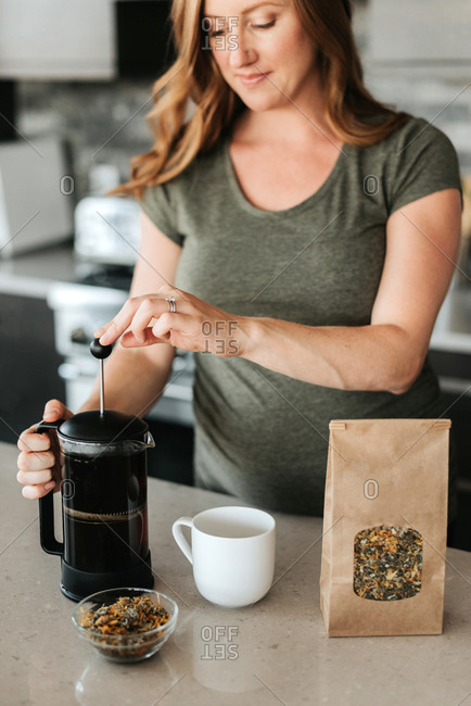 Pregnant woman brewing herbal tea with French press