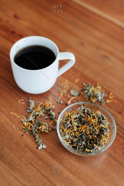 Mug of herbal tea and tea leaves
