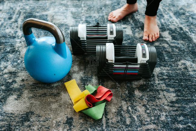 Kettle bell and assortment of exercise equipment by pair of feet