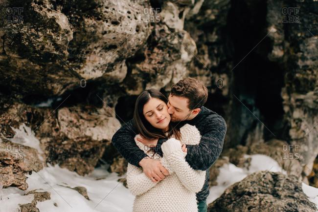 Couple hugging beside rock face, Tobermory, Canada