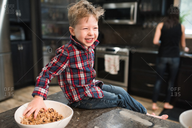 Toddler grabbing freshly baked vegetarian seed balls from bowl on kitchen worktop