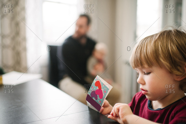 Boy playing at table, father in background