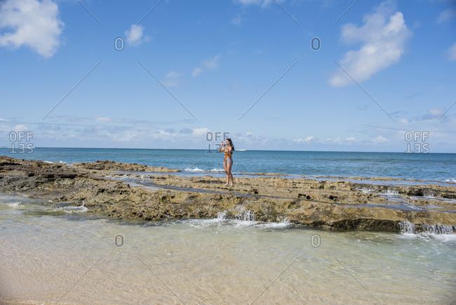 Woman taking photograph from sea, Waimea Canyon, Kauai, Hawaii