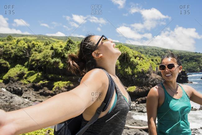 Hikers enjoying sunshine on coast of Waipipi Trail, Maui, Hawaii