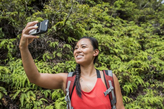 Hiker taking selfie in rainforest, Iao Valley, Maui, Hawaii