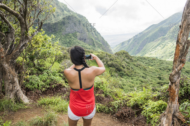 Hiker taking photograph of rainforest, Iao Valley, Maui, Hawaii