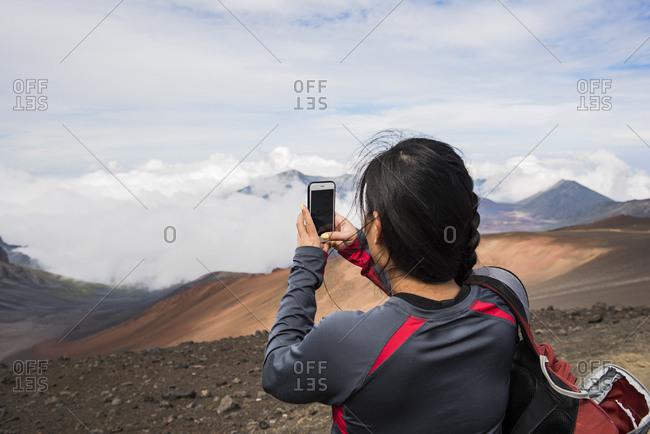 Hiker taking photograph, Haleakala National Park, Maui, Hawaii