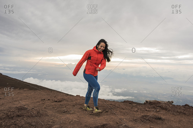 Woman walking along edge of mountain, Haleakala National Park, Maui, Hawaii