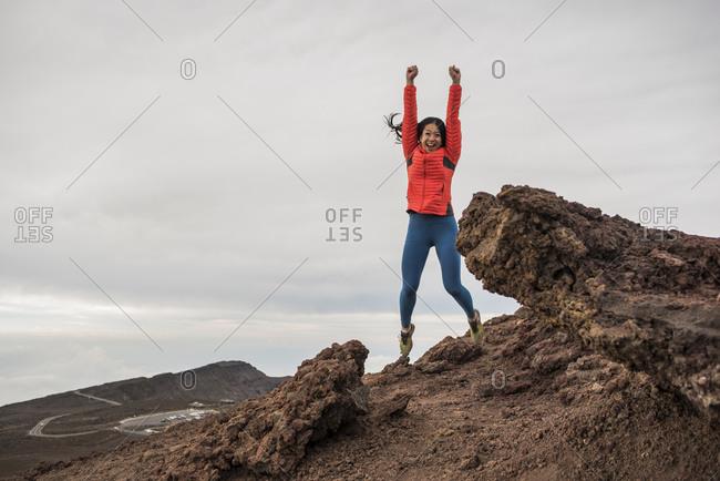 Happy woman at summit of mountain, Haleakala National Park, Maui, Hawaii