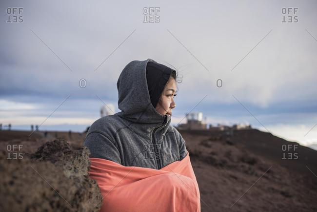 Woman hugging herself to warm up, Haleakala National Park, Maui, Hawaii
