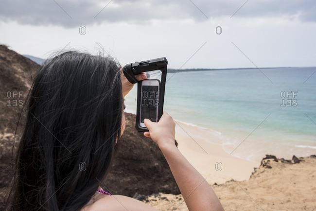 Woman taking photo on beach, Makena Beach, Maui, Hawaii