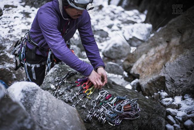 Climber preparing camming device on rock, Yosemite National Park, California, USA