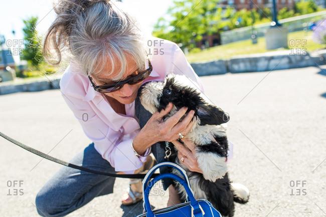 Senior woman petting cute dog in park