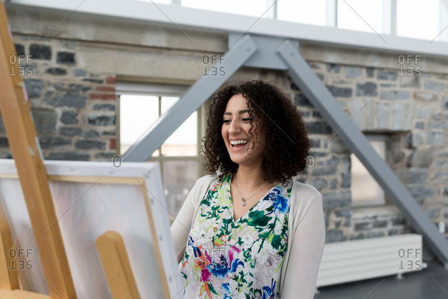 Young female painter laughing whilst painting canvas in studio