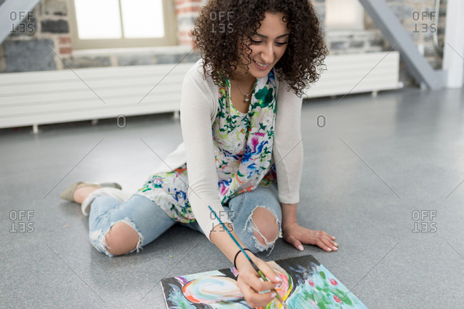 Young female painter painting canvas on studio floor