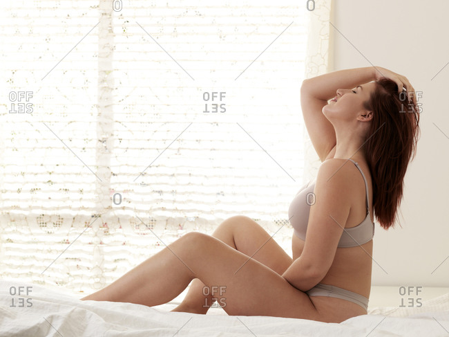 Beautiful curvaceous young woman wearing bra and knickers sitting up on bed with eyes closed and hand in hair