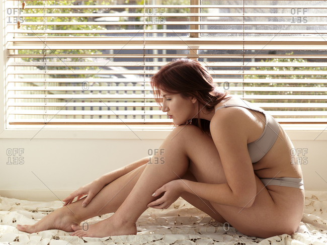 Beautiful curvaceous young woman wearing bra and knickers sitting up on bed touching ankle