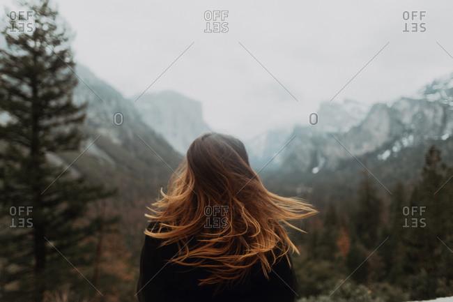 Young woman shaking long brown hair in mountain landscape, rear view, Yosemite Village, California, USA