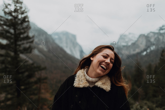 Young woman laughing in mountain landscape, head and shoulders, Yosemite Village, California, USA