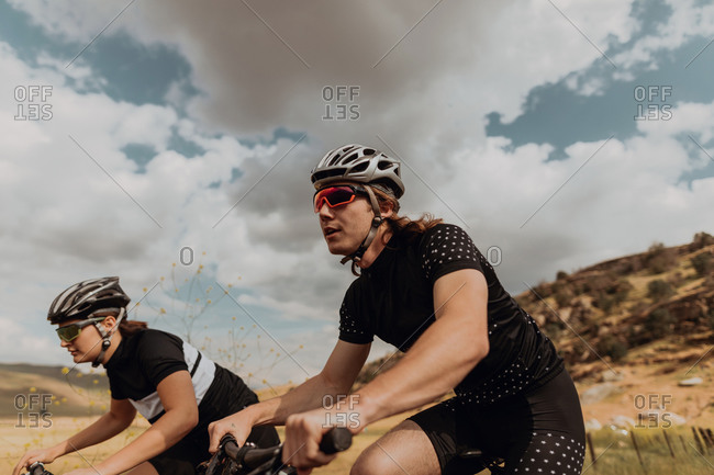 Young cycling couple cycling on rural road, side view, Exeter, California, USA
