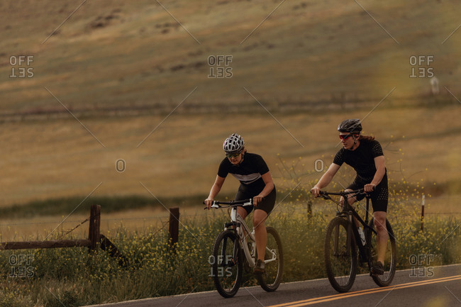 Young cycling couple cycling on rural road, Exeter, California, USA